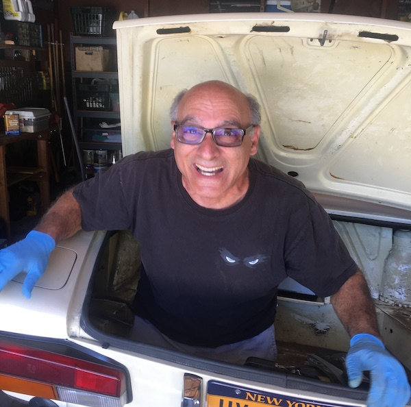 Larry stands on the ground through the trunk of his nephew's Fiat after they had removed the fuel tank.